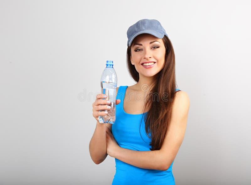 Acqua potabile della bella donna esile sportiva felice dalla bottiglia dopo la formazione sul fondo blu dello studio immagine stock libera da diritti