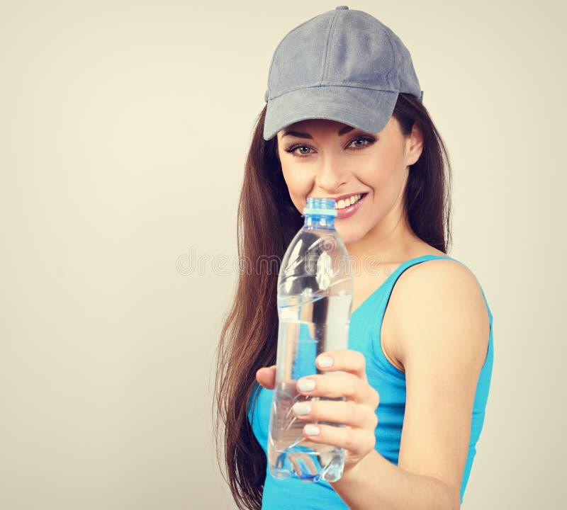 Acqua potabile della bella donna esile sportiva felice dalla bottiglia dopo la formazione sul fondo blu dello studio fotografia stock