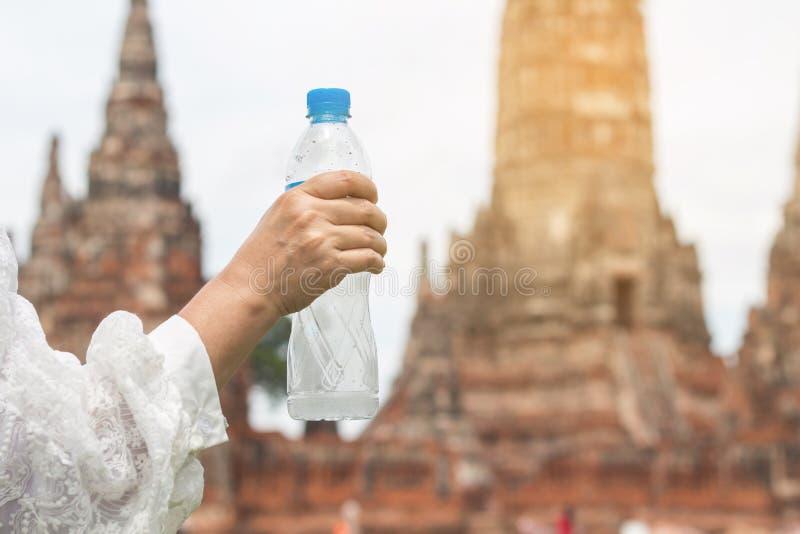 Acqua potabile della bella giovane donna asiatica dopo il riposo della passeggiata dentro fotografie stock libere da diritti