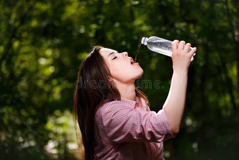 Acqua potabile della bella giovane donna assetata felice immagini stock libere da diritti