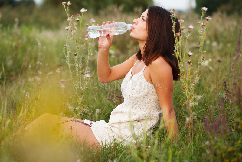 Acqua potabile della bella ragazza fotografie stock libere da diritti