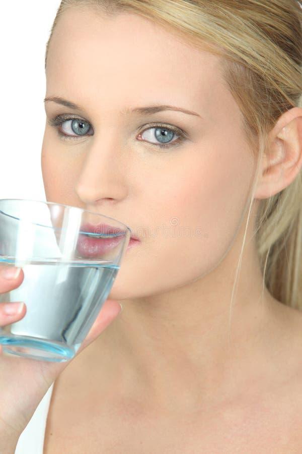 Acqua potabile della donna bionda fotografie stock libere da diritti