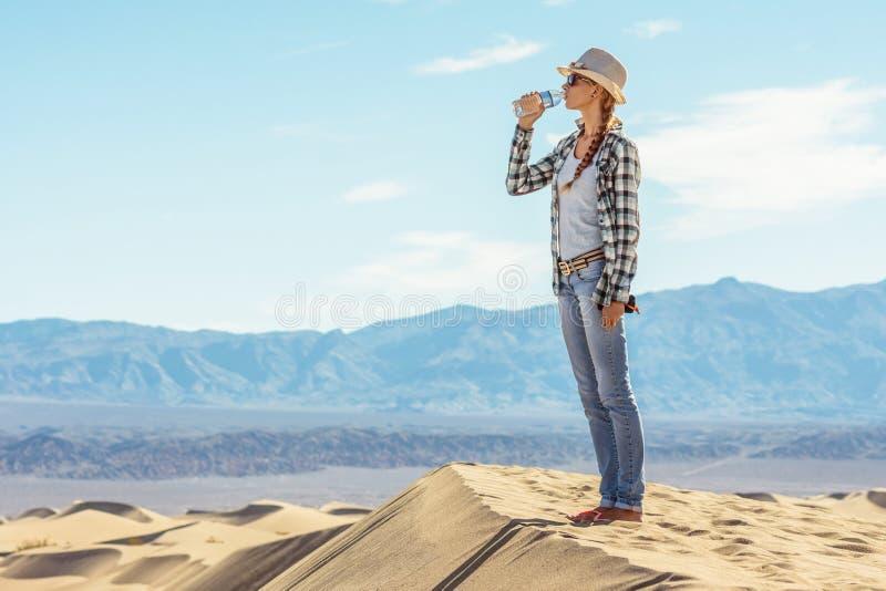 Acqua potabile della donna in deserto La ragazza attiva estigue la sete in Death Valley, la California, U.S.A. immagine stock