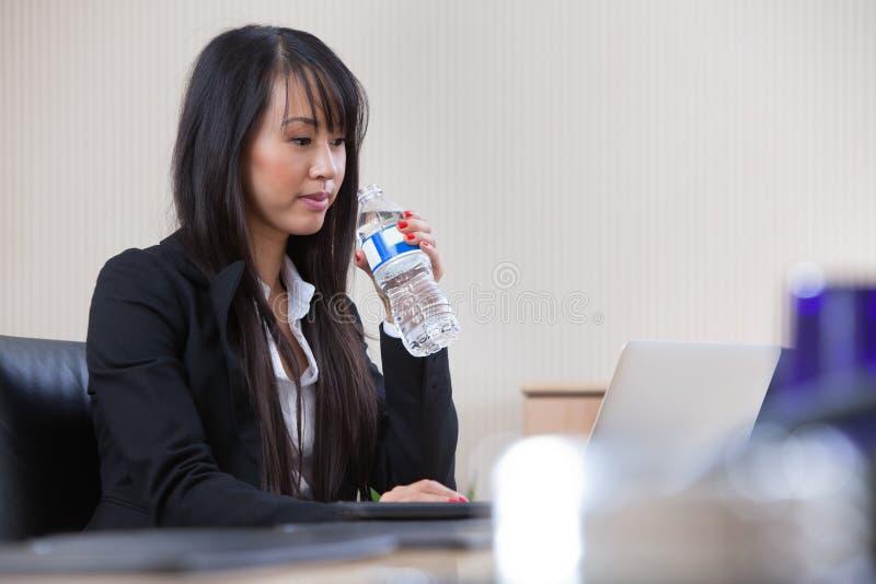 Acqua potabile della donna di affari sul lavoro fotografia stock libera da diritti