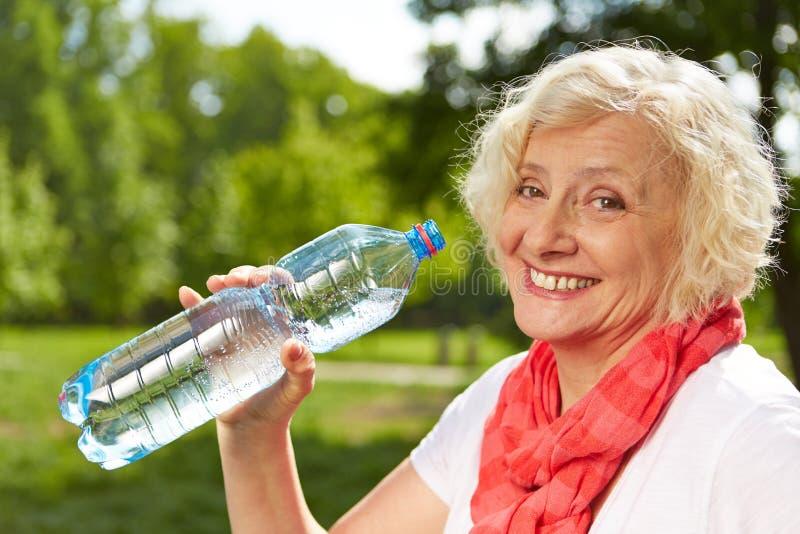 Acqua potabile della donna senior di estate immagini stock