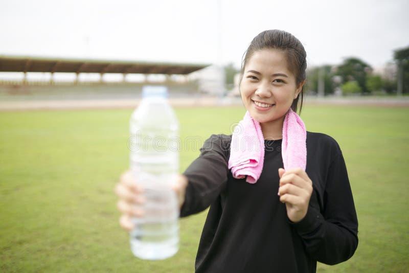 Acqua potabile della giovane donna asiatica fotografia stock