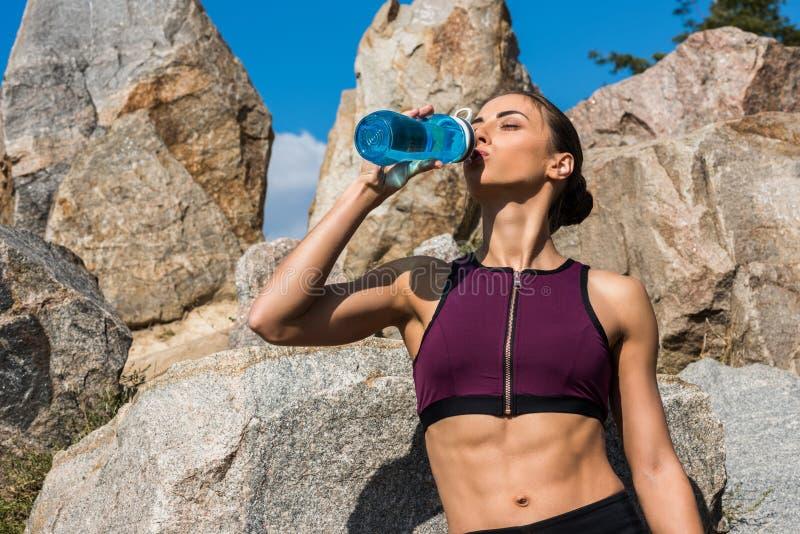 acqua potabile della giovane donna atletica nella parte anteriore immagini stock libere da diritti