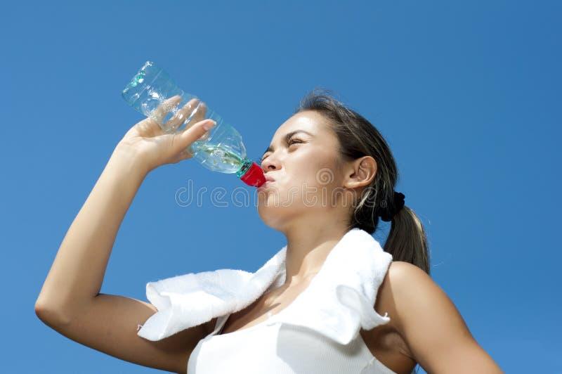 Acqua potabile della giovane donna dopo l'esercitazione fotografia stock libera da diritti