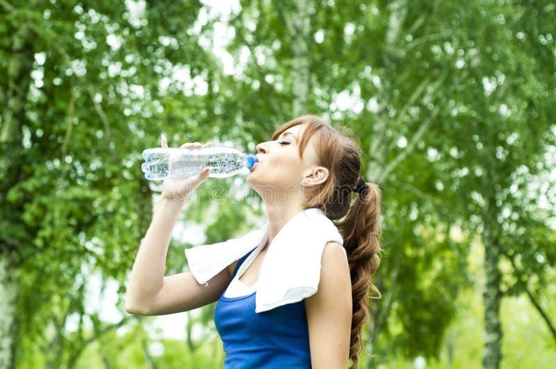 Acqua potabile della giovane donna dopo l'esercitazione fotografie stock