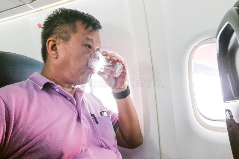 Acqua potabile della persona nel volo della lunga distanza dell'aeroplano all'idrato immagini stock libere da diritti