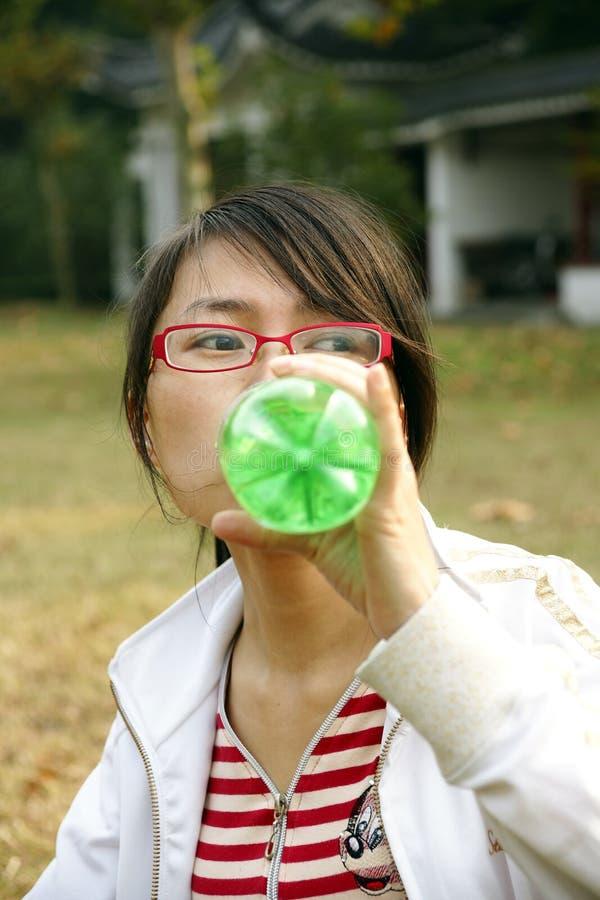 Acqua potabile della ragazza asiatica fotografia stock libera da diritti