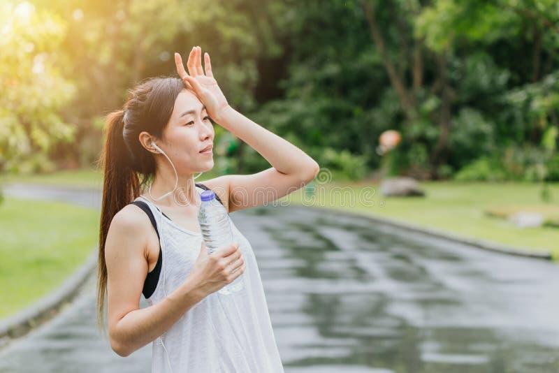 Acqua potabile della ragazza asiatica di sport per il giorno caldo sano di sport all'aperto fotografia stock libera da diritti