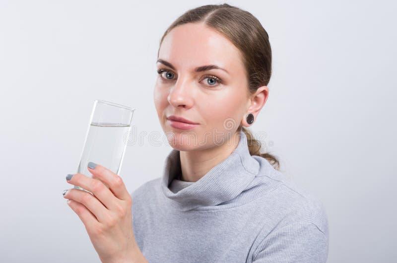 Acqua potabile della ragazza attraente su fondo leggero fotografia stock