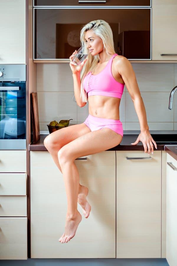 Acqua potabile della ragazza di forma fisica mentre sedendosi sul contatore di cucina fotografia stock
