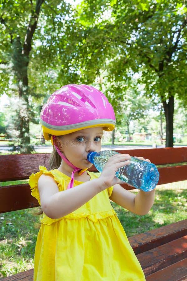 Acqua potabile della ragazza nel parco immagini stock libere da diritti