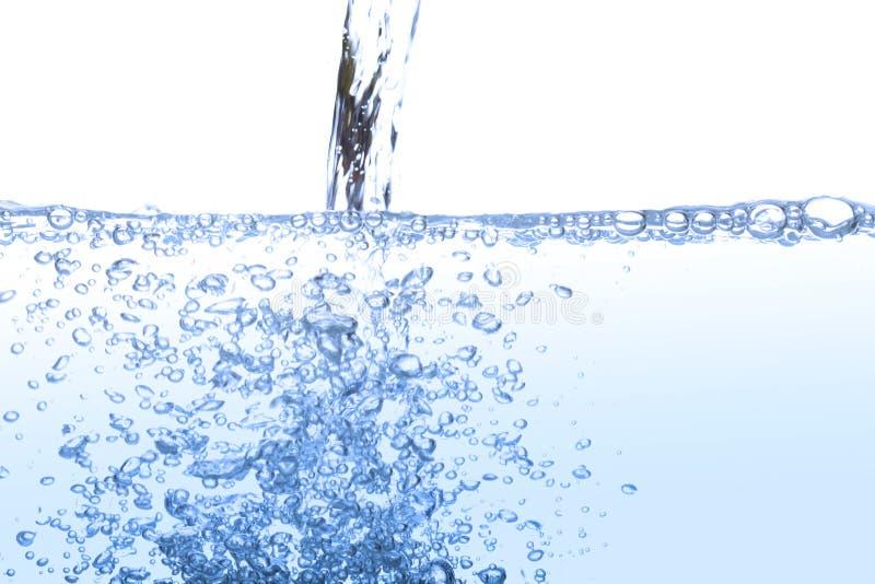 Acqua potabile di versamento con l'aria della bolla isolata su bianco immagine stock