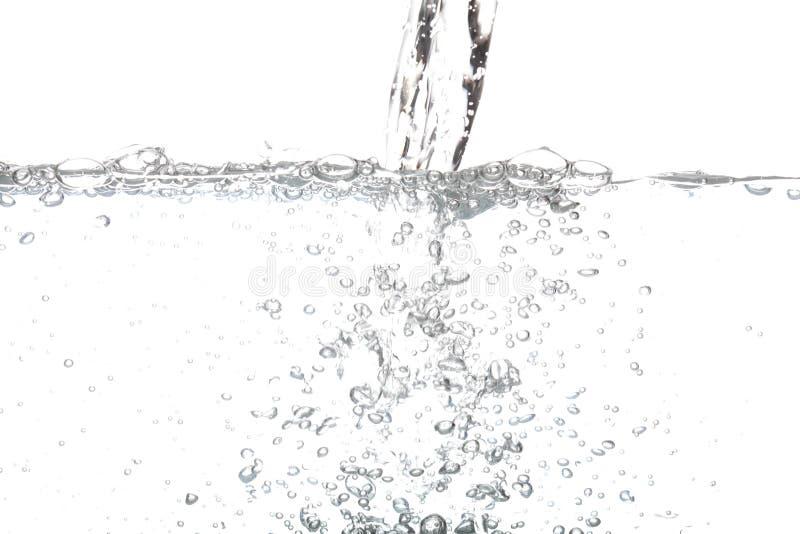 Acqua potabile di versamento con l'aria della bolla isolata su bianco immagini stock