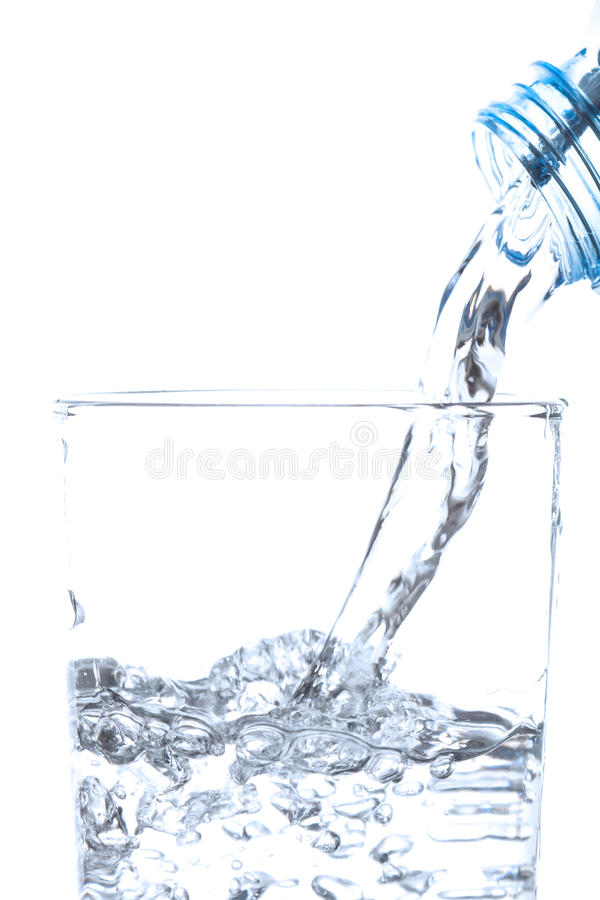 Acqua potabile di versamento dalla bottiglia in vetro su bianco immagine stock