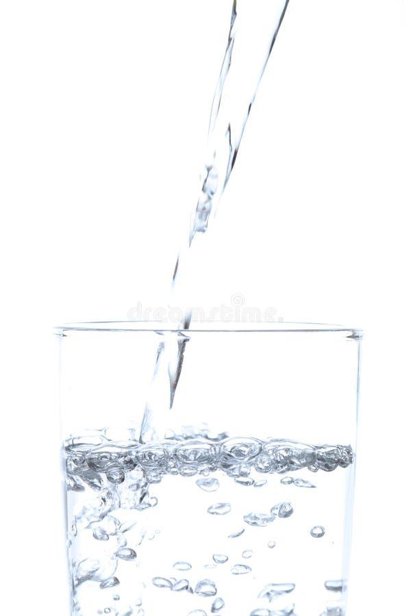 Acqua potabile di versamento in vetro con fondo bianco immagini stock