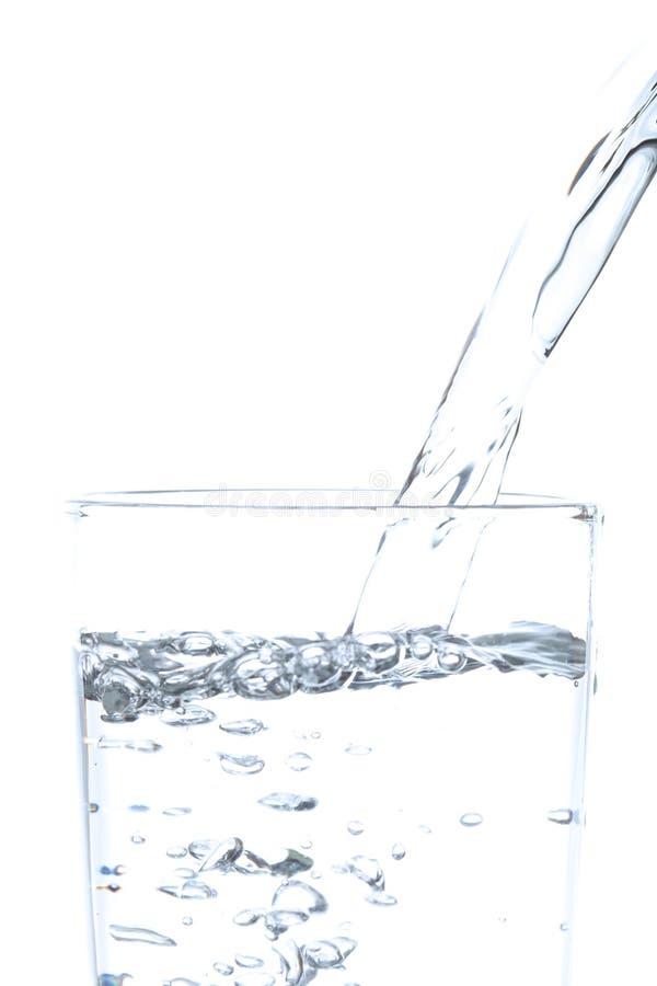 Acqua potabile di versamento in vetro con fondo bianco fotografie stock libere da diritti