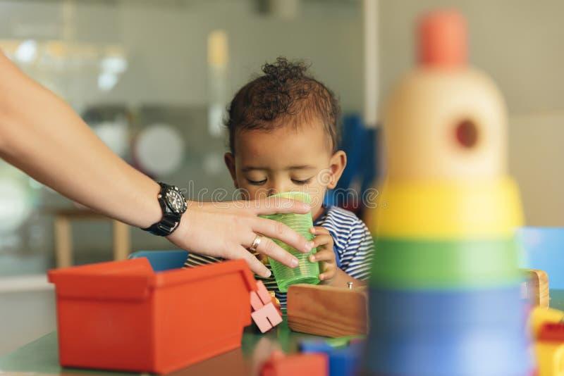 Acqua potabile e gioco del bambino felice immagini stock