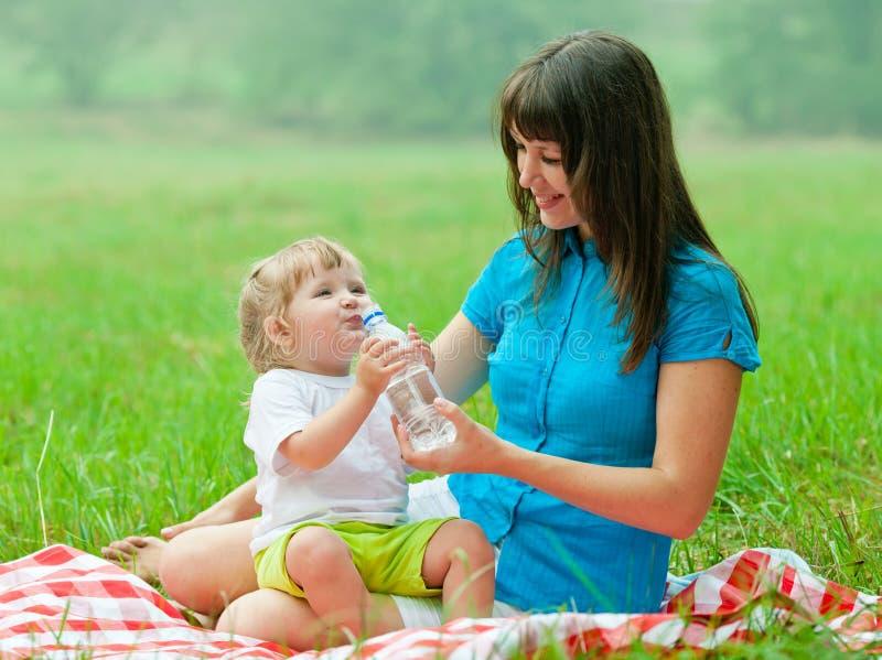 Acqua potabile felice del bambino e della madre dalla bottiglia immagine stock
