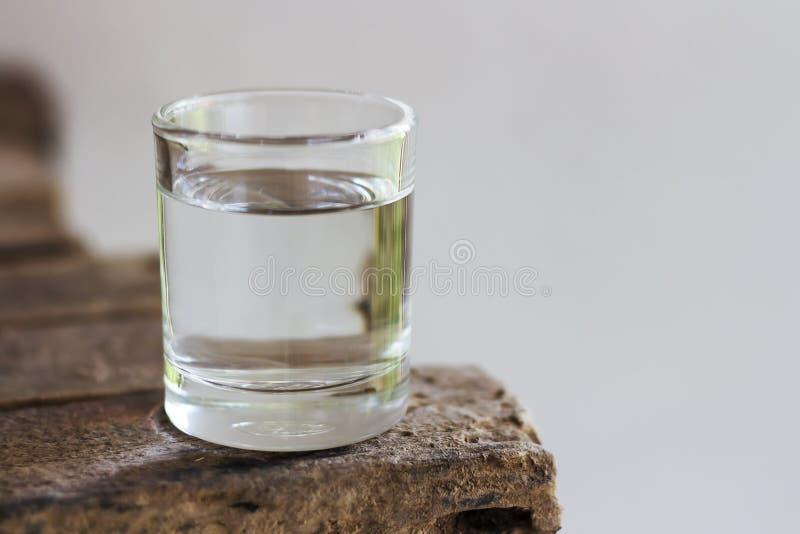 Acqua potabile in vetro su un pavimento di legno immagine stock