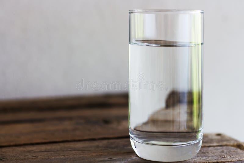 Acqua potabile in vetro su un pavimento di legno fotografia stock libera da diritti