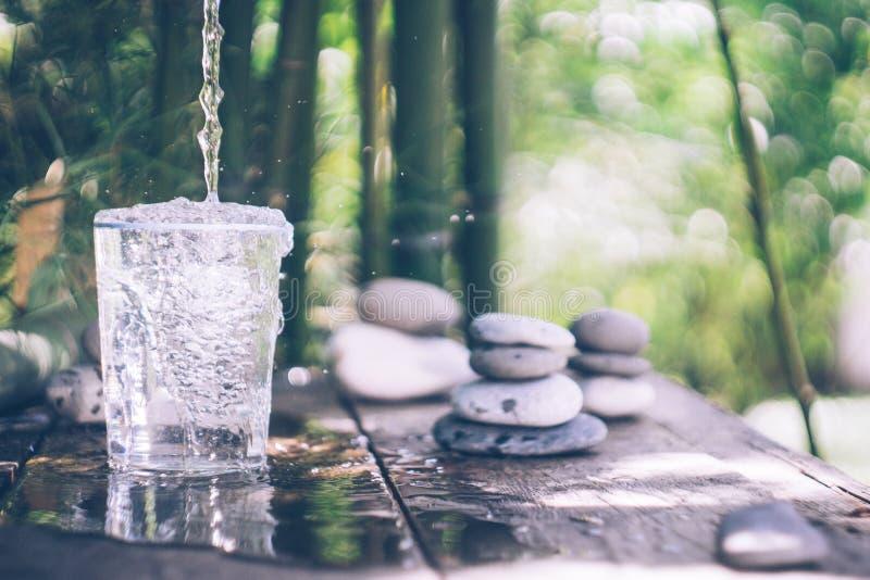 Acqua pulita che versa nel vetro accanto alle pietre sulla vecchia tavola Stile giapponese fotografia stock