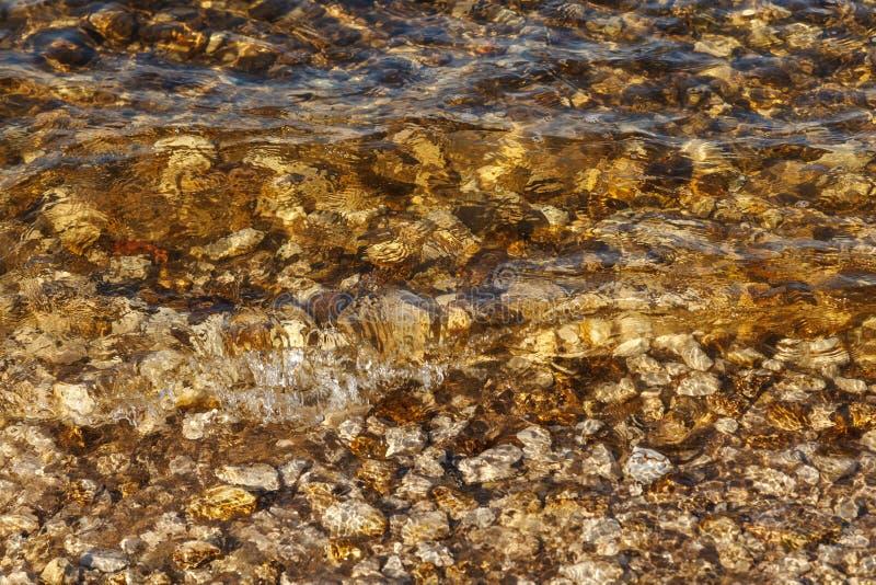 Acqua pulita delle onde del fiume vicino alla riva con un fondo roccioso Strutture astratte, rocce e sabbia del fondo nel fiume fotografie stock