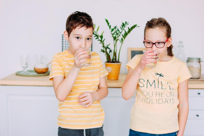 Acqua pulita sorridente della bevanda della ragazza e del ragazzo a casa immagine stock