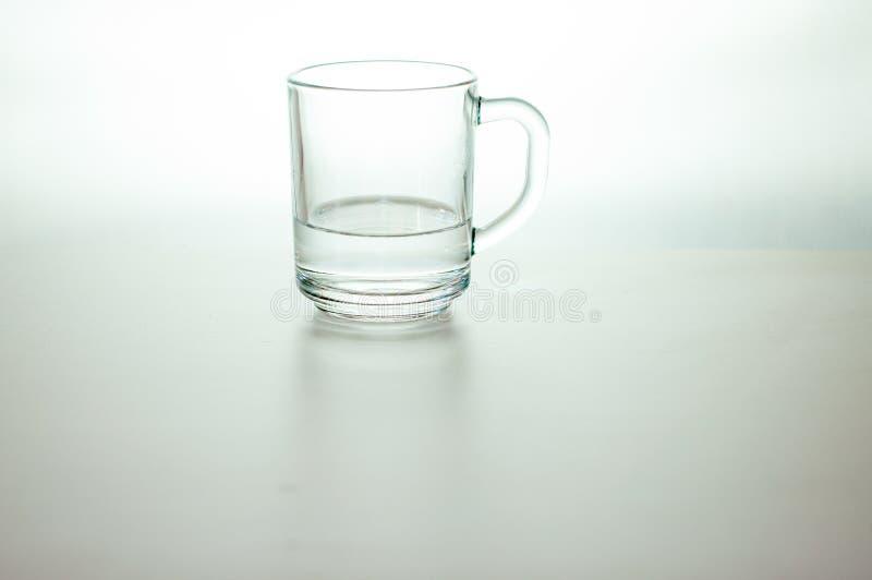 Acqua in vetro trasparente su fondo grigio ha purificato l'acqua fresca della bevanda fotografia stock