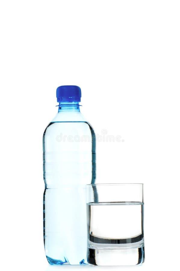 Acque in bottiglia e un vetro fotografie stock