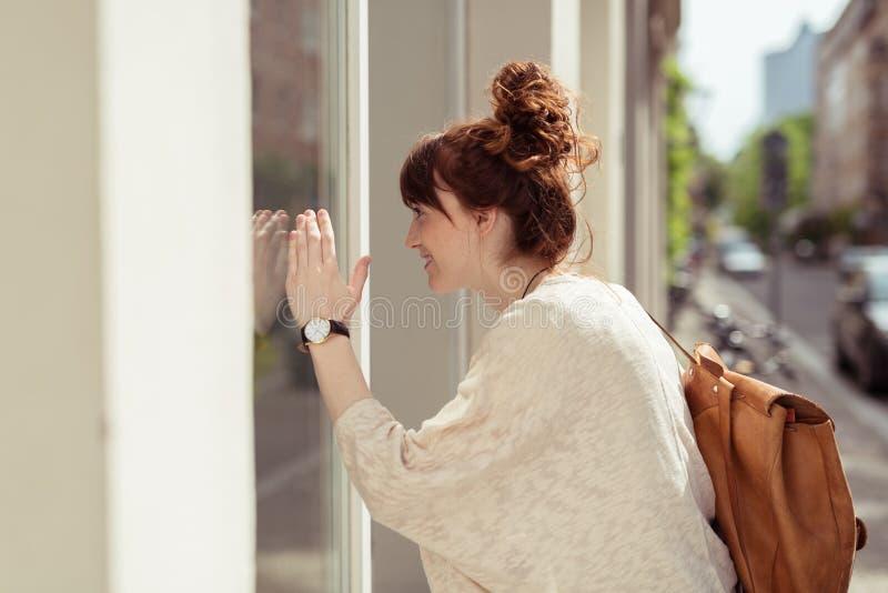 Acquisto abbastanza alla moda della finestra della donna della testarossa immagini stock