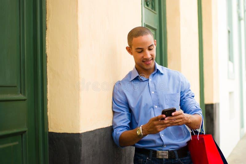 Acquisto afroamericano e invio di messaggi di testo dell'uomo sul telefono fotografia stock libera da diritti