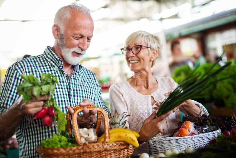 Acquisto, alimento, vendita, consumismo e concetto della gente - coppia senior felice che compra alimento fresco fotografie stock libere da diritti