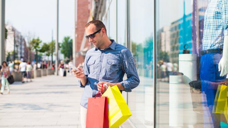Acquisto del giovane nel centro commerciale con molti sacchetti della spesa colorati in sua mano. Sta tenendo un telefono. immagini stock