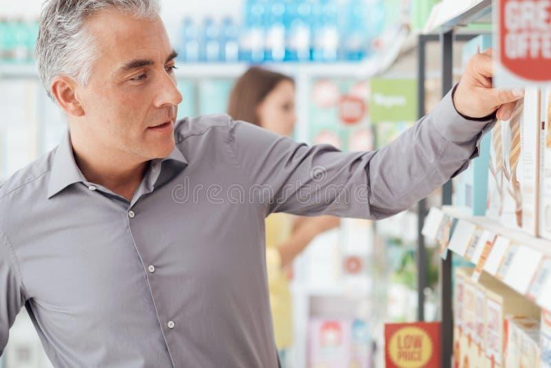 Acquisto dell'uomo al supermercato fotografia stock libera da diritti