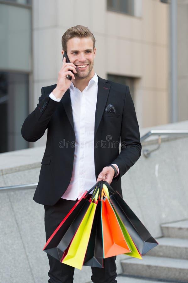 Acquisto dell'uomo d'affari L'uomo porta i sacchetti della spesa mentre abbia fondo urbano di conversazione telefonica Riuscito u fotografie stock