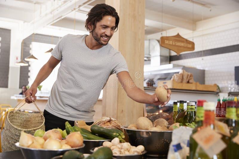 Acquisto dell'uomo per i prodotti organici in specialità gastronomiche immagini stock libere da diritti