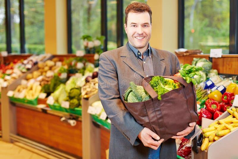 Acquisto dell'uomo per le verdure in supermercato immagine stock libera da diritti