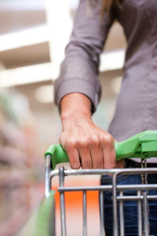 Acquisto della donna al supermercato con il carrello fotografia stock