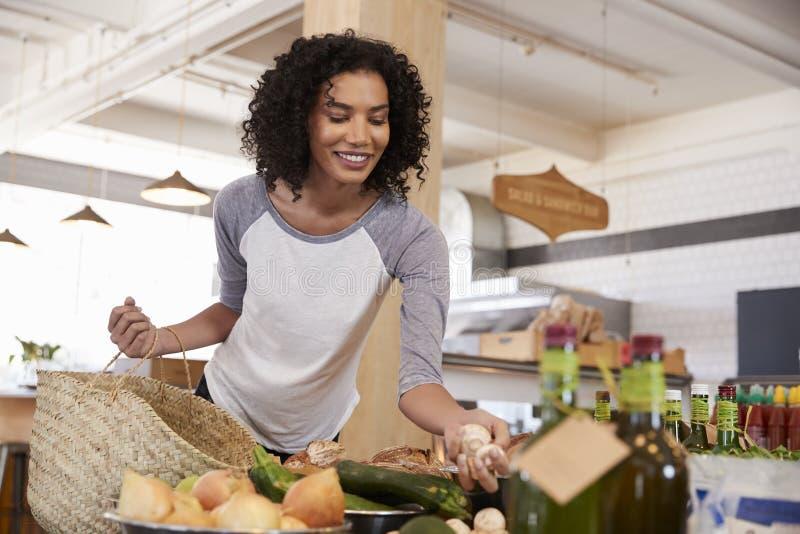 Acquisto della donna per i prodotti organici in specialità gastronomiche fotografia stock libera da diritti