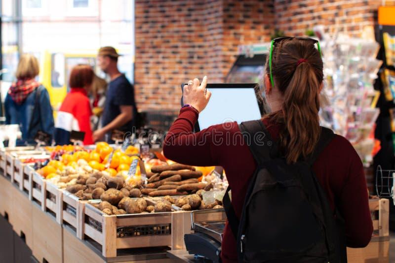 Acquisto della donna per la frutta e le verdure nel dipartimento dei prodotti di una drogheria/supermercato fotografia stock libera da diritti