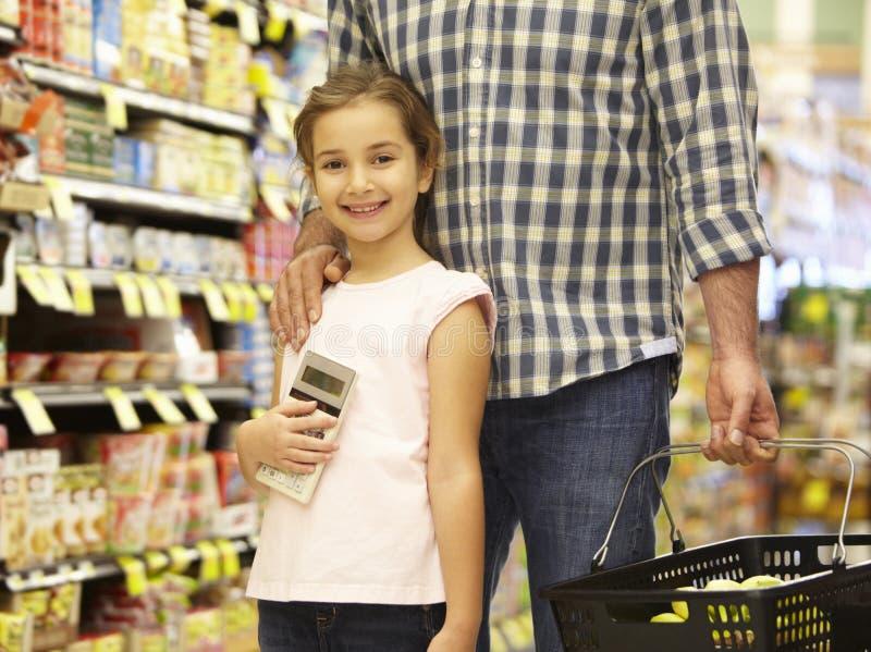 Acquisto della figlia e del padre nel supermercato fotografia stock libera da diritti