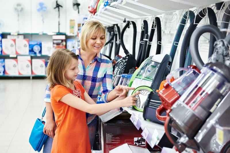 Acquisto della figlia e della madre per l'aspirapolvere elettrico fotografia stock libera da diritti