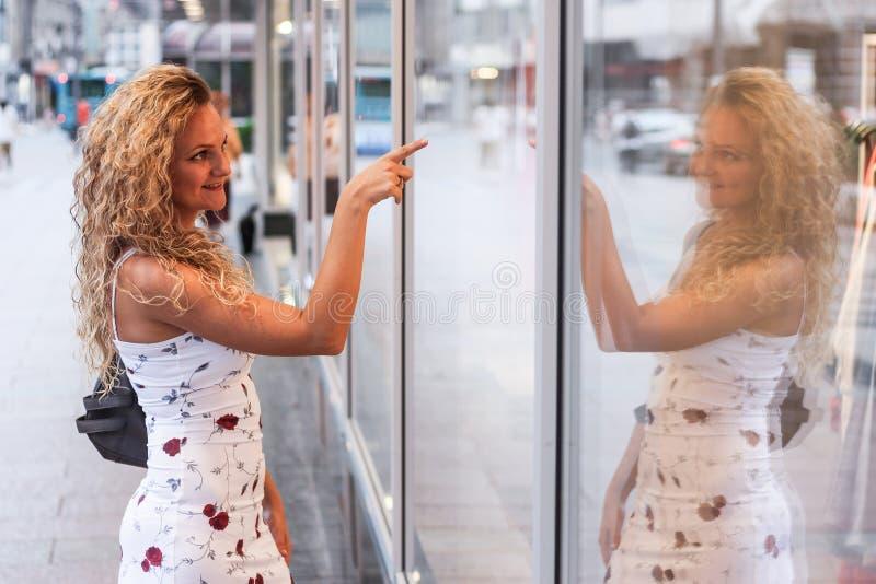 Acquisto della finestra - ragazza bionda riccia attraente che sta nella parte anteriore immagine stock