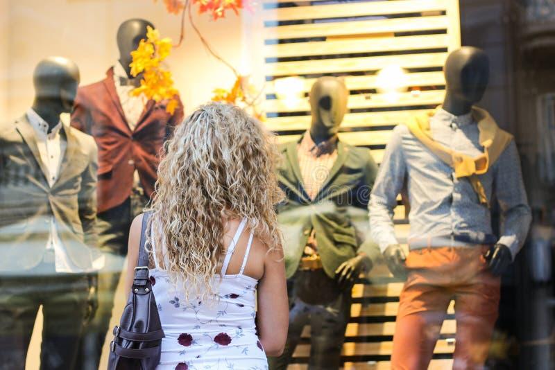 Acquisto della finestra - ragazza bionda riccia attraente che sta nella parte anteriore immagine stock libera da diritti