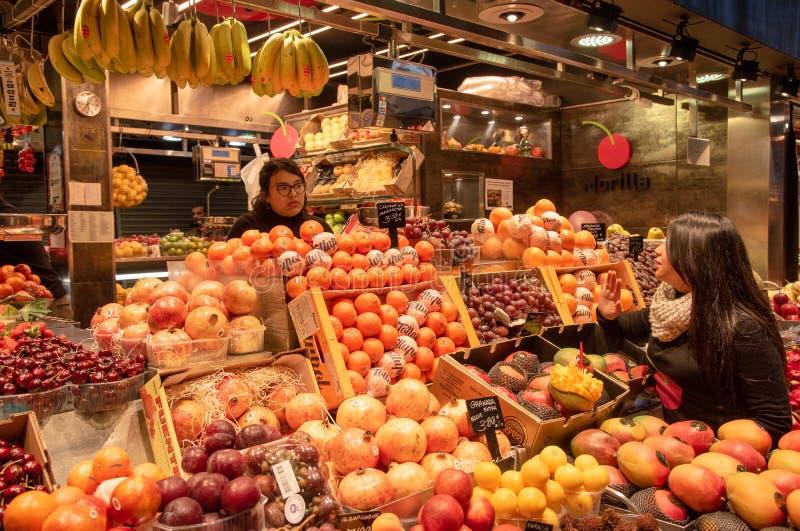 Acquisto della giovane donna ad un mercato di frutta fotografia stock