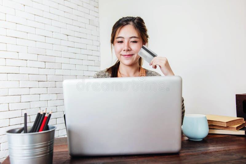 Acquisto della giovane donna o di fabbricazione dalla carta di credito e dal computer portatile pagamento a casa fotografia stock